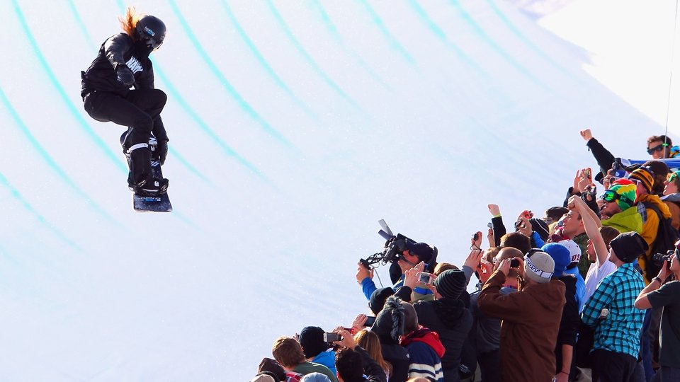 A snow boarder soars above the spectators during the Winter X Games