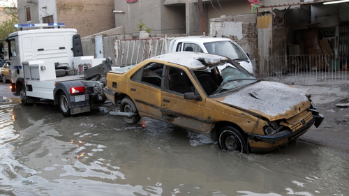 An Iraqi traffic police truck tows away a taxi cab after it was damaged in an explosion in the Karada district of Baghdad