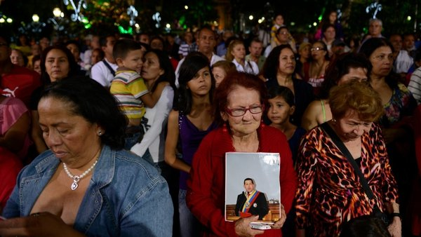 Supporters of Hugo Chavez pray during a mass in Caracas on 31 December