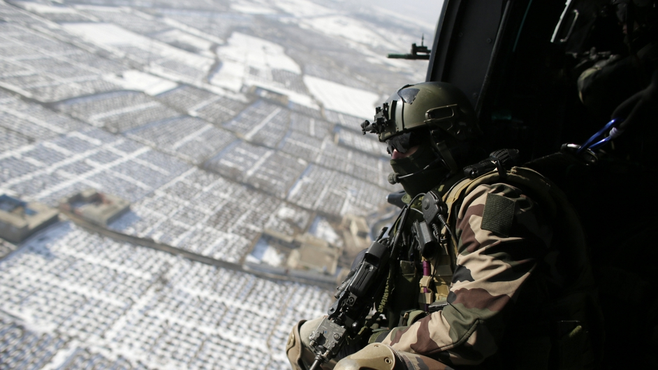 A French gunner sits in a military helicopter flying above Kabul