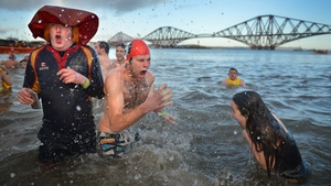 Over 1,000 New Year swimmers, many in costume, braved freezing conditions in the River Forth in front of the Forth Rail Bridge during the annual Loony Dook Swim in South Queensferry, Scotland