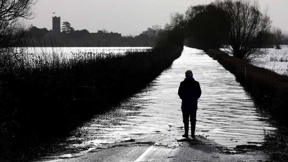 A man looks towards the village of Muchelney, which has been cut off by flooding on the Somerset Levels near Langport, England