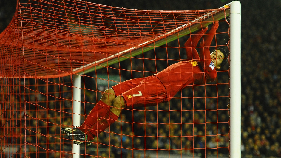 Liverpool player Luis Suarez swings on the cross bar following a missed chance during a match against Sunderland at Anfield