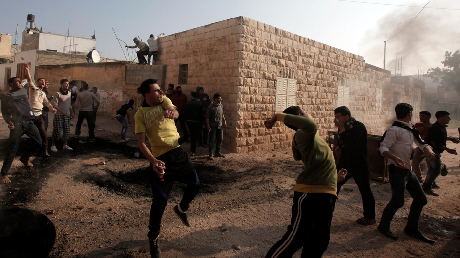 Palestinian protesters hurl stones at Israeli security forces during clashes in the West Bank village of Tamoun, near Jenin