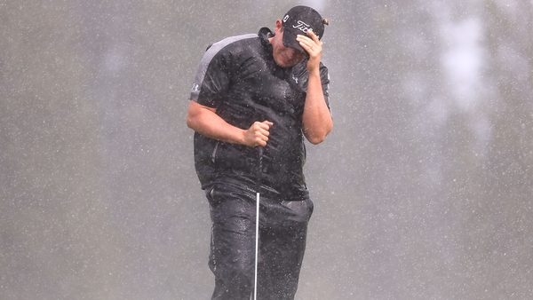 Scott Stallings shields himself from the wind and rain during the opening round
