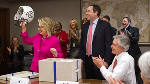 US Secretary of State Hillary Clinton receives a football helmet from Deputy Secretary Tom Nides (C) on her to work after recovering from hitting her head in a fall