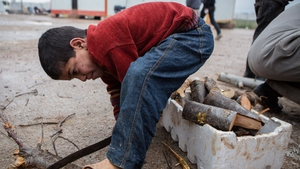 A Syrian boy cuts wood at a refugee camp near the city of Azaz on the Syria-Turkey border, home to more than 7,000 people