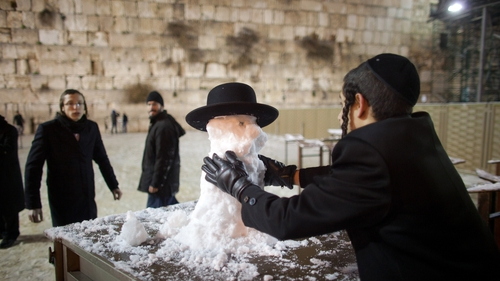 An ultra-Orthodox Jewish boy builds a snow man at the Western Wall in Jerusalem