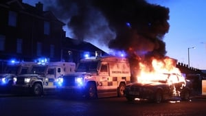 Police vehicles take up positions around a burning car during violence between loyalists, nationalists and the PSNI in east Belfast