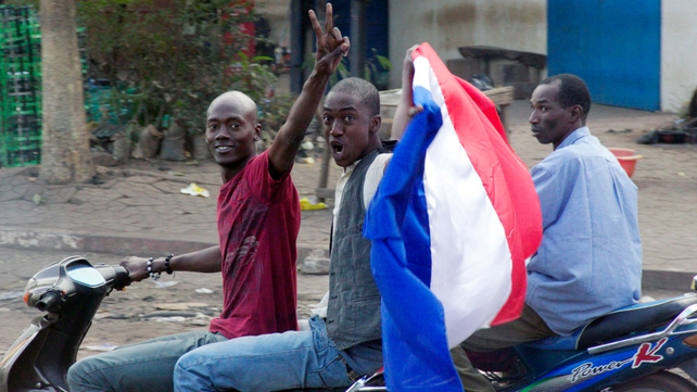 Malian people wave a French flag in Bamako as France send troops to help Malian forces hold back an advance by Islamist rebels