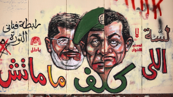 Graffiti depicting Egyptian President Mohamed Morsi (L), ousted president Hosni Mubarak (R) and former head of the army Field Marshal Mohammed Hussein Tantawi