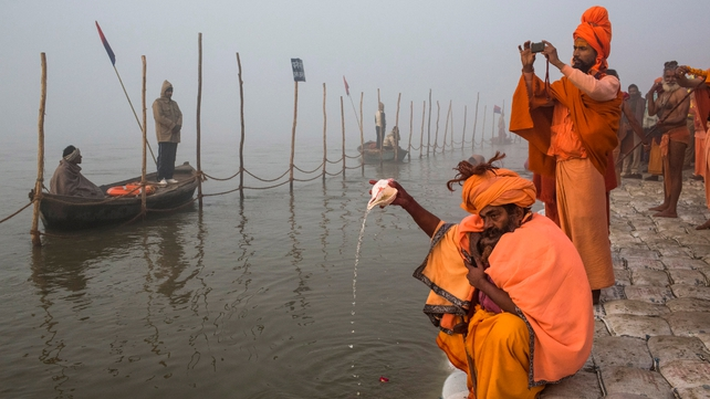 A Sadhu, Hindu holy man, pours water from a conch shell as he prays on the banks of the Ganges