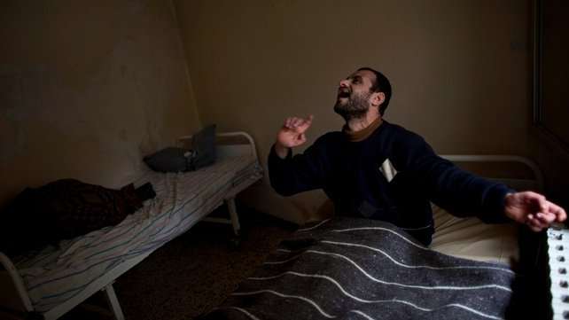 A Syrian patient sits in a bed at Dar Al-Ajaza psychiatric hospital in the heart of the Old City of Aleppo