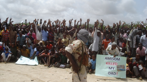 Somali men carry weapons during a demonstration organised by the islamist Al-Shabaab group