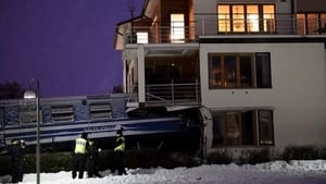Policemen stand in front of a local train that derailed into a residential building in Saltsjoebaden, Sweden