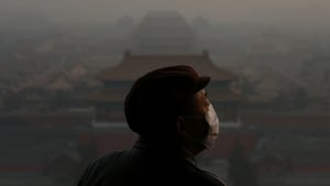 A tourist wearing a mask looks at the Forbidden City in Beijing as pollution covers the city