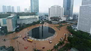 People and vehicles struggle through floodwaters in Jakarta's central business district