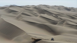 A lone biker crosses the dunes on the way from Pisco to Nazca on day three of the Dakar Rally