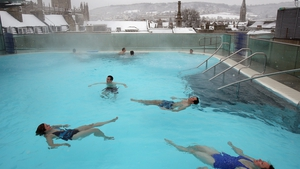 On the other side of the world, bathers enjoy the rooftop pool at a spa in Bath as snow falls across Britain