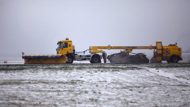 Snow ploughs clear the runway at Gatwick Airport yesterday