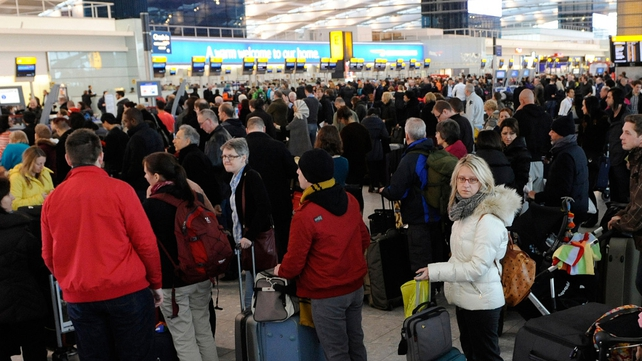 Passengers queue at for the check-in desks at Heathrow airport after hundreds of flights were cancelled