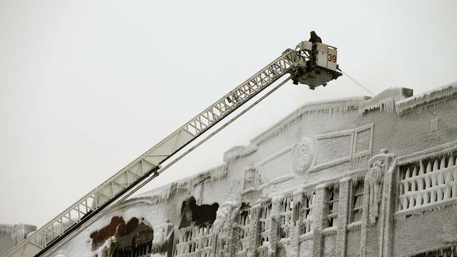 Firefighters work to tackle the blaze at the ice-covered warehouse