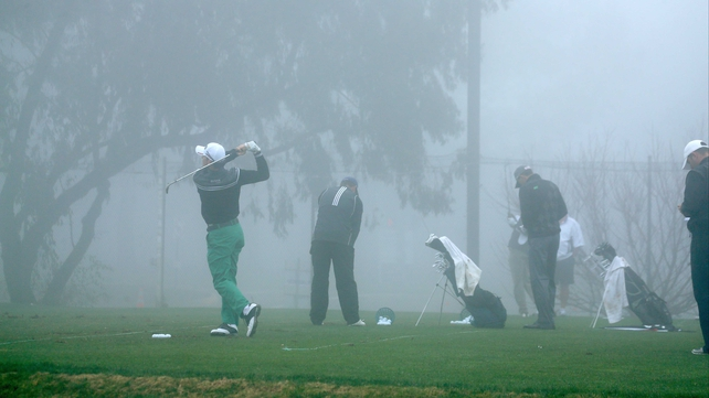 Players hit balls on the practice range during a fog delay