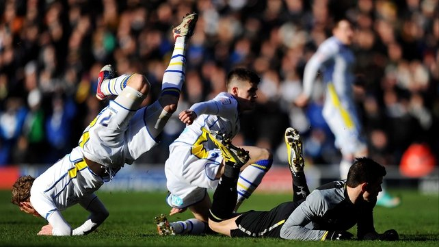 Paul Green of Leeds hurdles the grounded Gareth Bale