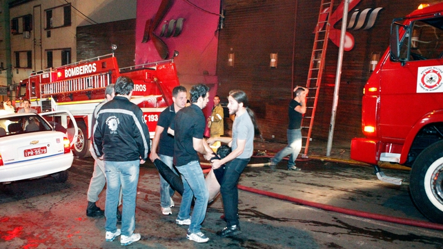 A victim of the nightclub fire in Brazil is carried from the scene