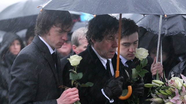 Ms Price's sons, Danny (L) and Oscar (R), stand with her ex-husband Stephen Rea at Milltown cemetery in Belfast