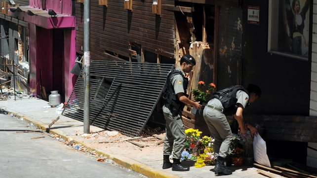 Policemen leave flowers at the scene of the blaze