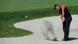 Tiger Woods plays out of the bunker on the 10th