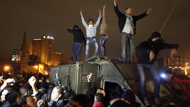 Protesters stand on a police vehicle in Cairo's Tahrir Square