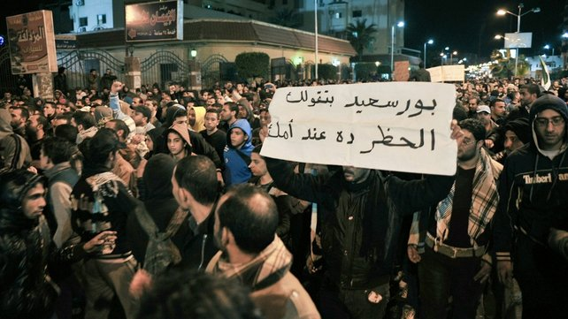 Protesters break a curfew on the streets of Port Said last night