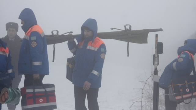 Paramedics stand in thick fog near the site of the plane crash
