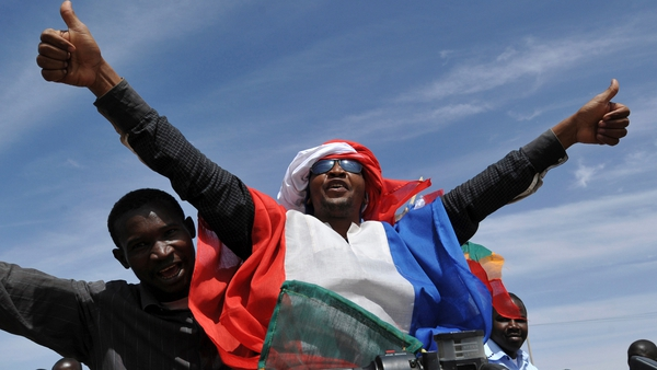 Youths celebrate with the French flag in Ansongo, a town south of the northern Malian city of Gao, as Niger troops enter the city