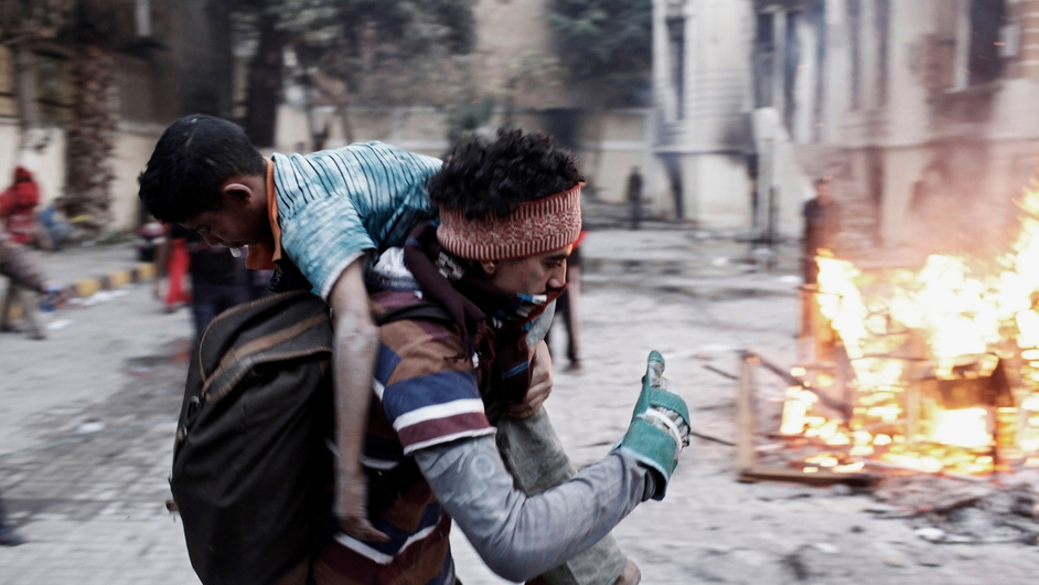 An Egyptian protester carries an injured boy away from clashes with Egyptian riot police during a protest in Port Said