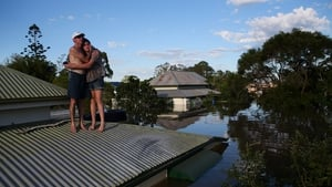 A man and his daughter stand on their roof as parts of southern Queensland experiences record flooding