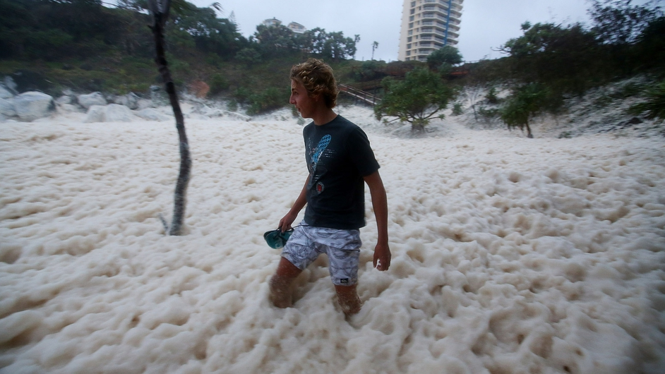A man walks through ocean foam in Snapper Rocks as Queensland experiences severe rains and flooding from Tropical Cyclone Oswald