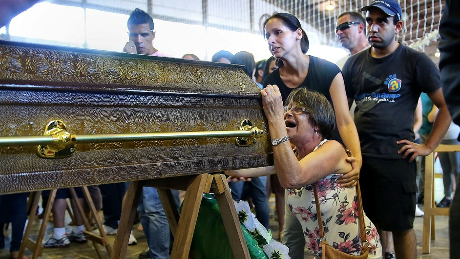 Relatives mourn the loss of a loved one following a fire at Kiss nightclub in Santa Maria, Brazil