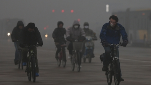 Cyclists wear face masks as air pollution in Beijing remains at a dangerous high