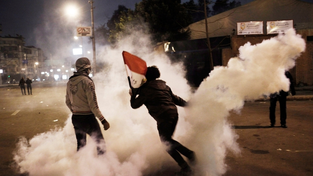 A protester throws a tear gas canister back towards police in Cairo