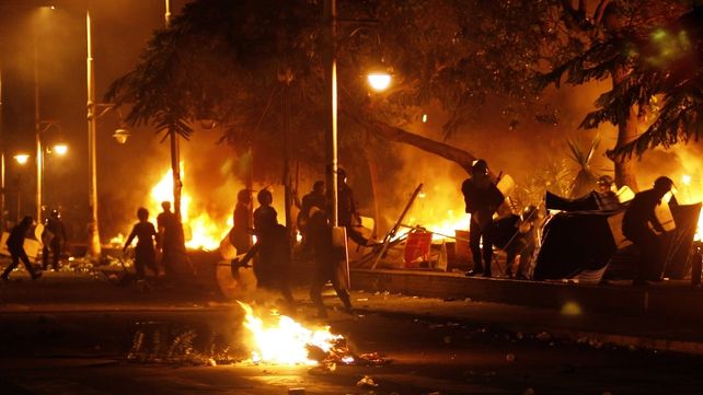 Egyptian riot policemen set fire to the tents of the protesters in front of the gate of the presidential palace in Cairo