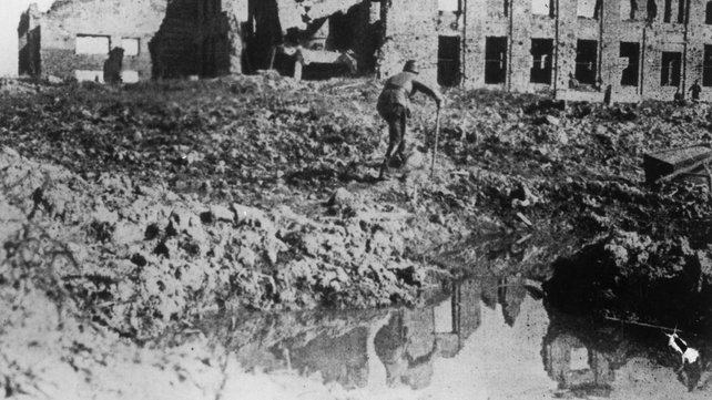 Circa 1943: A lone German soldier hobbles round a waterlogged crater in which are reflected the devastated buildings of Stalingrad