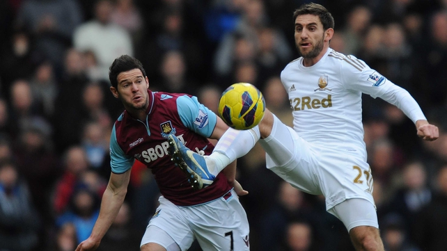 Angel Rangel of Swansea City holds off the challenge of West Ham's Matt Jarvis