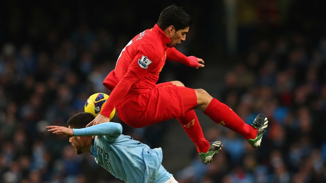 Luis Suarez of Liverpool tangles with Javi Garcia of Manchester City