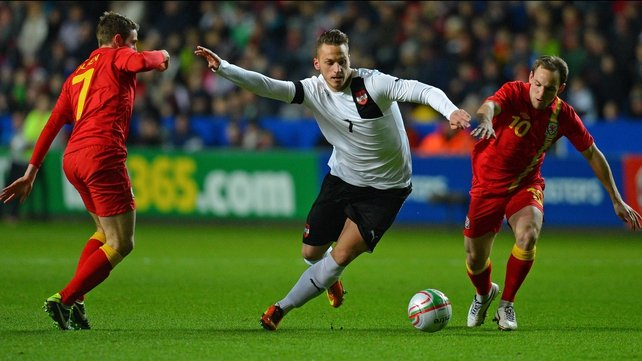 Marko Arnautovic vies with Wales midfielders David Vaughan (R) and Joe Allen (L)