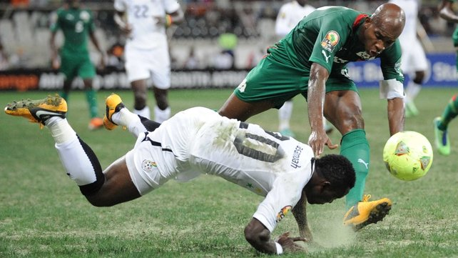 Tumbling Ghana midfielder Kwadwo Asamoah and stumbling Ghana star Charles Kabore fight a losing battle to maintain their footing on a woeful playing surface in Nelspruit