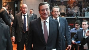 Mario Draghi, President of the European Central Bank (ECB) arrives for the press conference as RTÉ reporter George Lee looks on