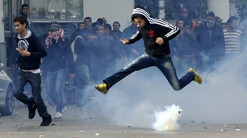 A Tunisian protester jumps over smoke after police fired teargas during a rally outside the interior ministry